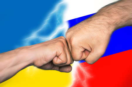 imperialism: Political metaphor. Russian Ukrainian conflict. Two men bumping fists against Ukrainian and Russian flags. Motion blur