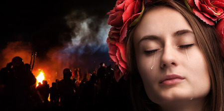 riots: Patriotic concept. Ukraine in fire. Close-up portrait of beautiful crying girl with tears on her cheeks against the background of mass riots