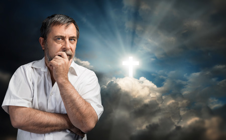 Religious conversion concept. Elderly man thinking about faith and God. Portrait against the sky with a glowing cross symbol of faith. Reklamní fotografie