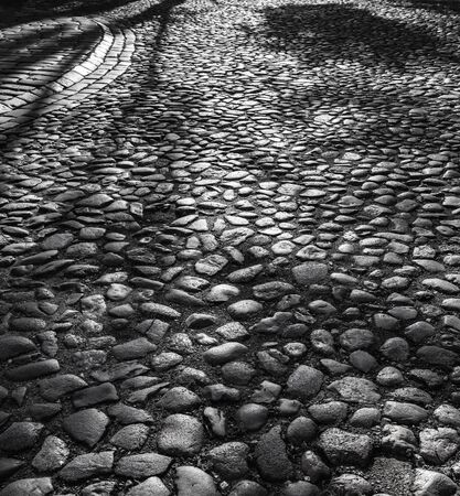 kaunas: Abstract background of cobble stone road. Early morning shadows in old Kaunas
