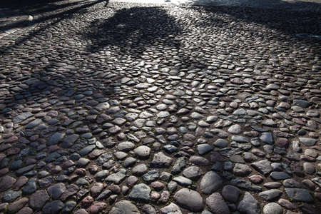 Abstract background of cobble stone road. Early morning shadows in old Kaunas