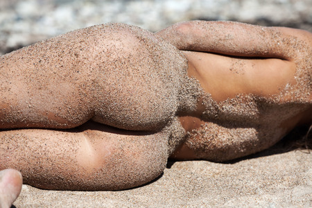 Young nude woman covered by sand resting on a sandy beach near the sea
