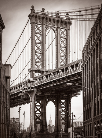 Manhattan Bridge and Empire State Building seen from Brooklyn, New York. Old photo stylization, film grain added. Sepia toned 免版税图像