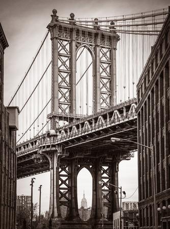 Puente de Manhattan y el Empire State Building ven desde Brooklyn, Nueva York. Foto vieja estilización, añadió grano de la película. tonos sepia