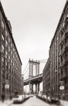 manhatan: Manhattan Bridge and Empire State Building seen from Brooklyn, New York. Black and white image with a blurred foreground. Old photo stylization, film grain added. Sepia toned Stock Photo
