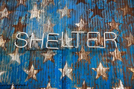 rusty fence: Word shelter made up of neon tubes on the background of a stylized image fragment of an American flag on a rusty fence Stock Photo