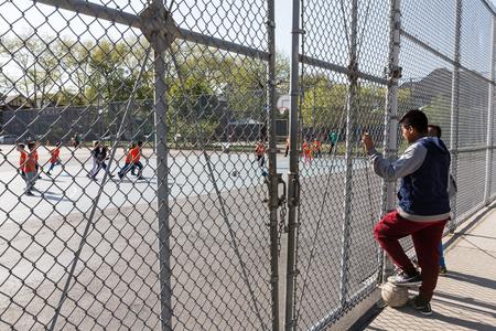 futbol infantil: NEW YORK, USA - Apr 27, 2016: Boys watch the children play football in the childrens playground in Brooklyn, New York City