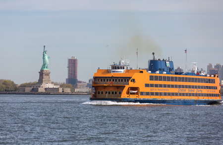 staten: NEW YORK, USA - Apr 28, 2016: Staten Island Ferry passing Statue of Liberty in New York Harbor. Staten Island Ferry is a passenger ferry service operated by New York City Department of Transportation