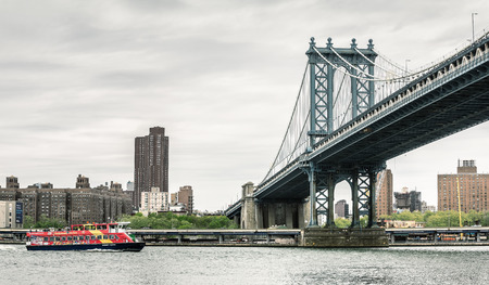 waterways: NEW YORK, USA - Apr 29, 2016: Manhattan Bridge and CitySightseeing Skyline Cruise boat with harbor cruise and sightseeing tour of NYC and its famous waterways Editorial