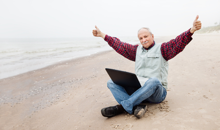 Free lifestyle concept. Happy senor businessman sitting on the beach on a foggy day with a laptop and enjoys a successful deal photo