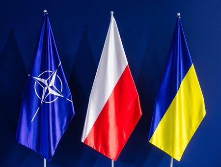 nato summit: WARSAW, POLAND - Jul 9, 2016: Flags of NATO, Poland and Ukraine at the NATO summit in Warsaw