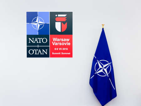 north atlantic treaty organization: WARSAW, POLAND - Jul 9, 2016: Emblem and the flag of the North Atlantic Treaty Organization (NATO) sammit in Poland
