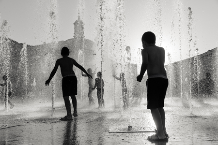 Silhouette Of A Group Happy Children Playing In Water Fountain The Light