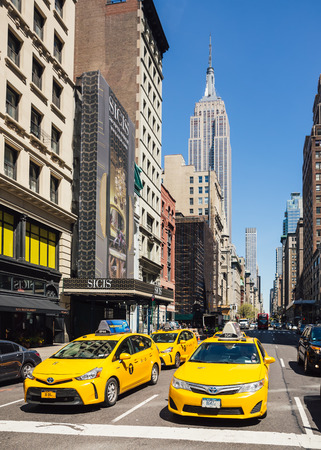 fifth avenue: NEW YORK, USA - Apr 30, 2016: Yellow taxi car on Fifth Avenue in Manhattan with views on Empire State Building