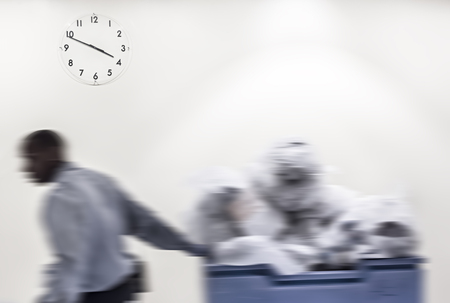 Passage of time concept. Blurred image of black man carries the cart with garbage against wall background with a clock
