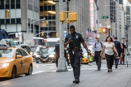 NEW YORK, USA - Sep 21, 2016: Manhattan street scene. Black police officer with a mobile phone on the streets of New York City in the evening time Editorial