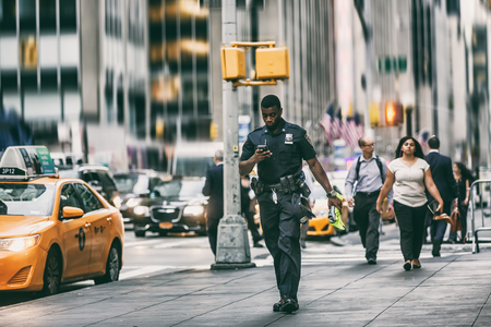 NEW YORK, USA - Sep 21, 2016: Retro look Manhattan street scene. Black police officer with a mobile phone on the streets of New York City in the evening time