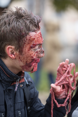KIEV, UKRAINE - Oct 30, 2016: Zombie Walk. Young people taking part in a zombie parade in the streets of Kiev, to celebrate Halloween. Street performer in Halloween costume and makeup.