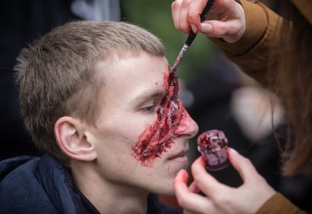 KIEV, UKRAINE - Oct 30, 2016: Zombie Walk. Young people taking part in a zombie parade in the streets of Kiev, to celebrate Halloween. Young man gets bloody makeup Editorial