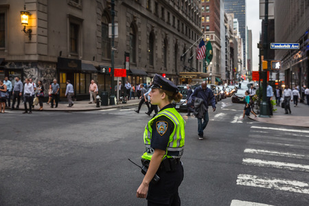 NEW YORK, USA - Sep 20, 2016: New York and New Yorkers. Manhattan street scene. Young woman police officer at Manhattan streets in evening time Editorial
