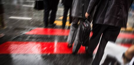 cross street: People cross street at crosswalk on a rainy day in the city. Intentional motion blur