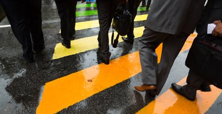 cross street: People cross street at crosswalk on a rainy day in the city Stock Photo