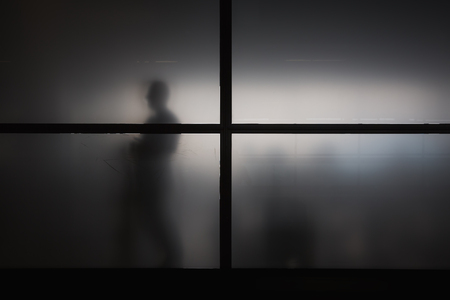 disillusionment: Silhouette of man behind window with matted glass