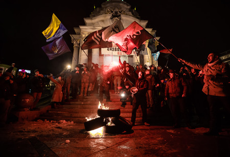 activists: KIEV, UKRAINE - Nov 21, 2016: Activists of nationalist groups burn tyres in Independence Square as they gather to mark the anniversary of 2014 Ukrainian pro-European Union mass protests