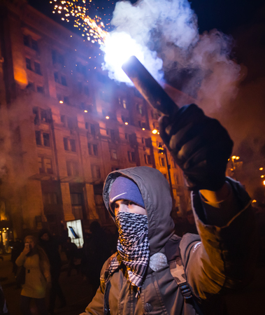 flambeau: KIEV, UKRAINE - Nov 21, 2016: Men burn flares during a rally held by activists of nationalist groups and their supporters who mark the anniversary of 2014 Ukrainian pro-European Union mass protests