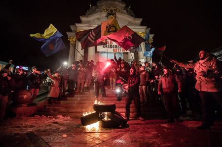 the nazis: KIEV, UKRAINE - Nov 21, 2016: Activists of nationalist groups burn tyres in Independence Square as they gather to mark the anniversary of 2014 Ukrainian pro-European Union mass protests