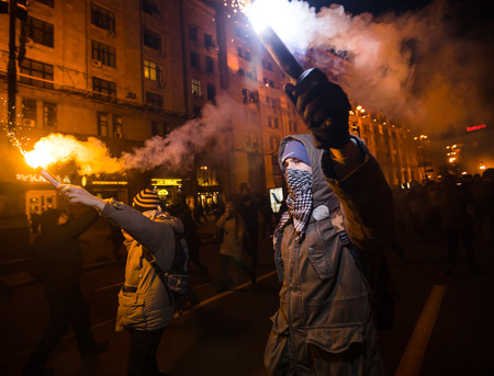 activists: KIEV, UKRAINE - Nov 21, 2016: Men burn flares during a rally held by activists of nationalist groups and their supporters who mark the anniversary of 2014 Ukrainian pro-European Union mass protests
