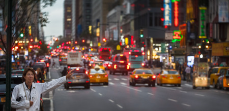 NEW YORK, USA - Sep 20, 2016: Manhattan street scene. Woman waits for a taxi on the streets of New York City in evening time. Blurred cars lights on background Editorial