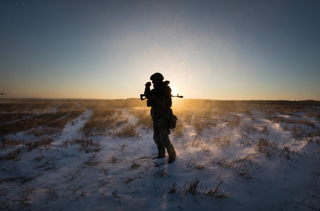 antiterrorist: DONETSK REGION, UKRAINE - Dec 05, 2016: Silhouette of military man in a snow-covered field on Karatchoun mountain near the Kramatorsk town, Donetsk region Editorial