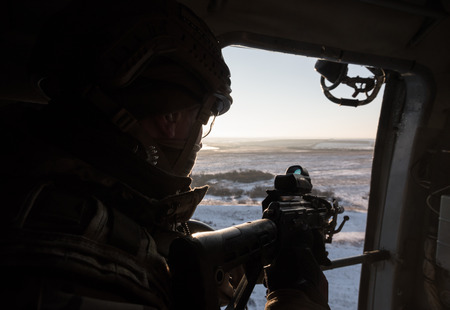 antiterrorist: DONETSK REGION, UKRAINE - Dec 05, 2016: Soldiers of Armed Forces of Ukraine with guns on board of Ukrainian army helicopter during a combat mission in area of antiterrorist operation in Donetsk region