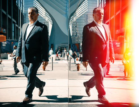NEW YORK, USA - Sep 22, 2016: Manhattan reflections street scene. New York and New Yorkers. An elderly man in a suit on the streets of NYC. Film cross process stylization Editorial