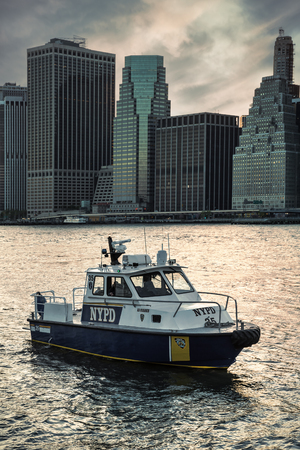 NEW YORK, USA - May 01, 2016: New York City Police Department boat patrolling in the East River in evening time. New York City Police Department is the largest municipal police force in United States Editorial