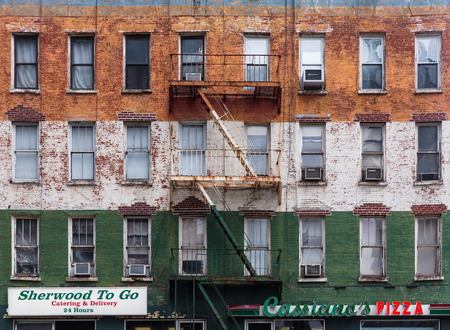 NEW YORK, USA - May 01, 2016: Facade of an old building in Manhattan. Brick wall with peeling off paint and escape fire ladders Sajtókép