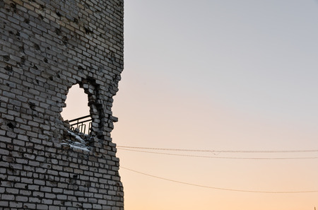artillery shell: DONETSK REGION, UKRAINE - Dec 18, 2016: Destroyed houses and ruins, mechanisms, chaos and deserted village due to the war in eastern Ukraine. Hole in the wall of an artillery shell Editorial
