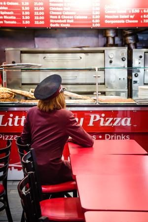 expects: NEW YORK, USA - May 02, 2016: Young woman in a burgundy suit and cap sitting at a red table in the pizzeria and expects to pizza Editorial