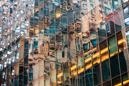 manhattan mirror new york: Abstract NYC background. Glass facade of a skyscraper in New York City with a mirror reflections of houses and streets of Manhattan