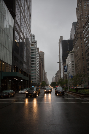 NEW YORK, USA - May 02, 2016: Cars lights on the streets of Manhattan on an overcast rainy day