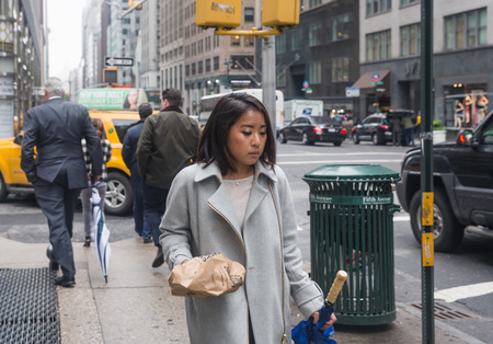 madison: NEW YORK, USA - May 03, 2016: Madison avenue in NYC. Manhattan street scene. Girl of the Asian appearance in a hurry about her business. Editorial