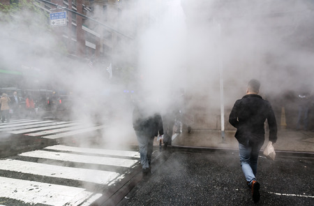 piped: NEW YORK, USA - May 03, 2016: Manhattan street scene. Cloud of vapor from the subway on the streets of Manhattan in NYC. Typical view of Manhattan Editorial