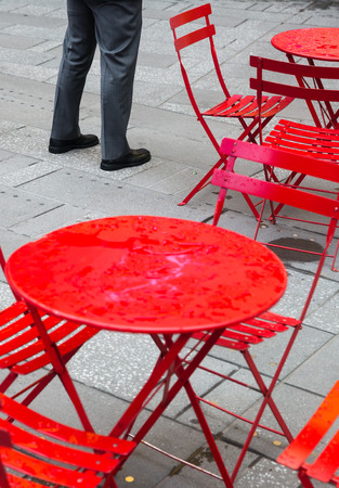 seating area: Manhattan street scene. Seating area in Times Square. Elegant man in a suit standing near the red tables and chairs. Stock Photo