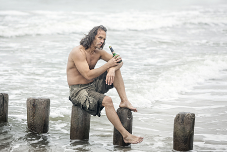 Alcoholism. Middle-aged man with a naked torso sits on wooden poles on the beach and drinking alcohol Stock Photo