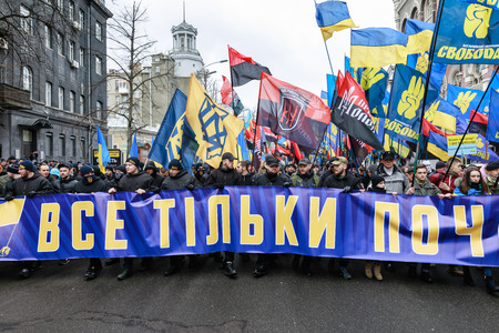 militant: KIEV, UKRAINE - Feb 22, 2017: Activists of nationalist groups during the March of National Dignity. Inscription on the poster - Everything is just beginning