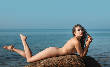 Naked girl outdoors enjoying nature. Beautiful young nude woman lies on large stones against the sea. Lady with nude perfect body on the nudist beach. Summer paradise. Free Happy Woman