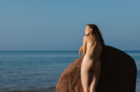 Naked girl outdoors enjoying nature. Beautiful young nude woman stands among the big stones against the sea. Lady with nude perfect body on the nudist beach. Summer paradise. Free Happy Woman