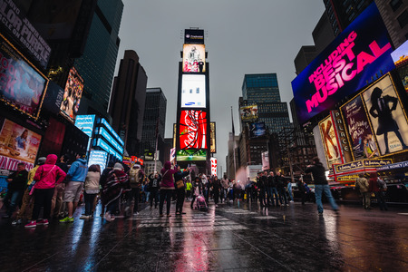 NEW YORK, USA - Apr 30, 2016: Times Square in the evening on a rainy day. Crowds of Americans and tourists in the square brightly adorned with billboards and advertisements
