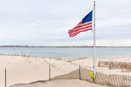 American flag on the beach of Breezy Point. Breezy Point is a neighborhood in the New York City borough of Queens, located on the western end of the Rockaway peninsula. Manhattan in the background